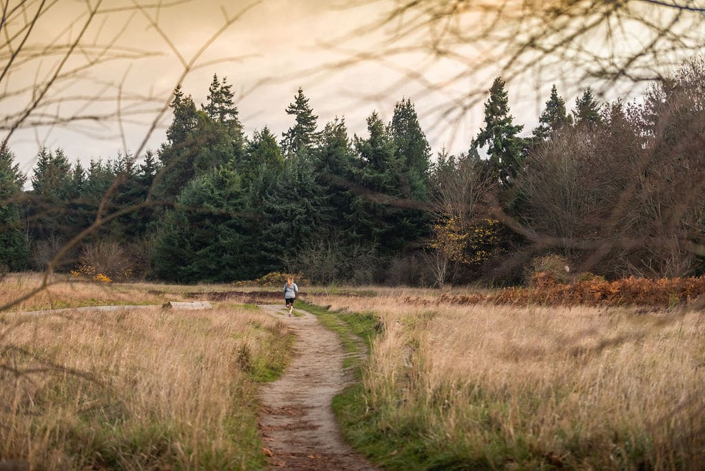 Woman running on trails near Discovery Park in Seattle
