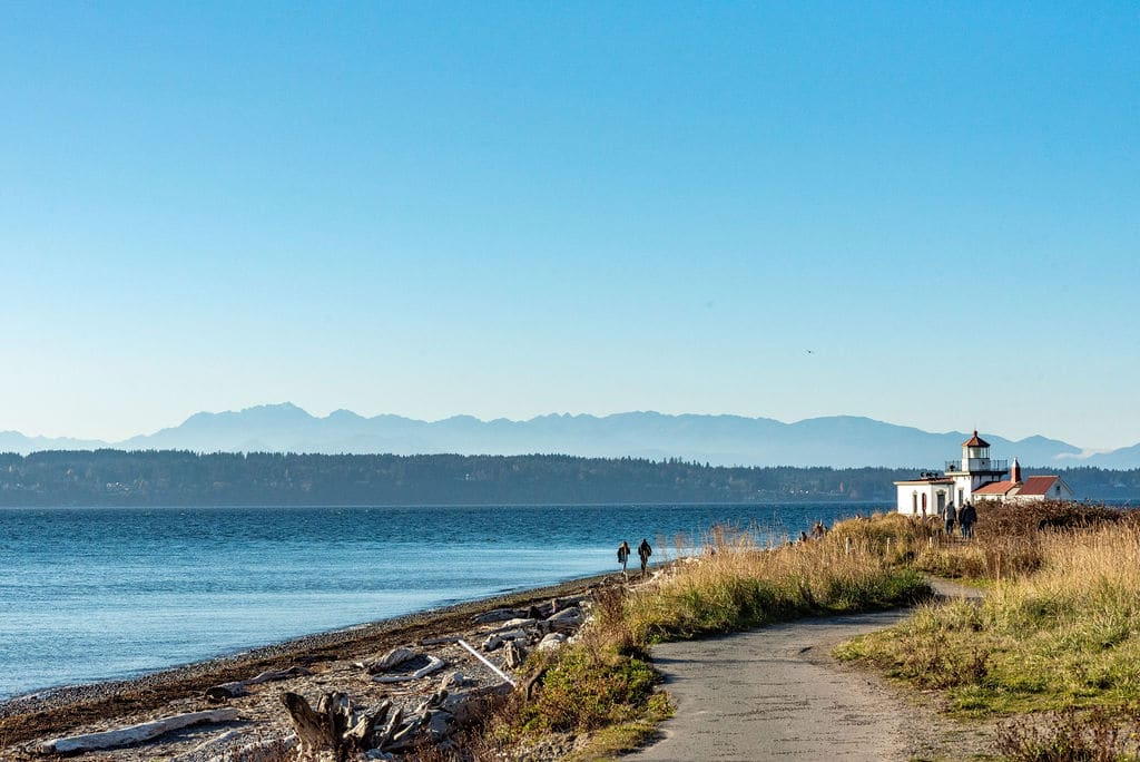 People walking on beach near Seattle lighthouse with mountains in background.