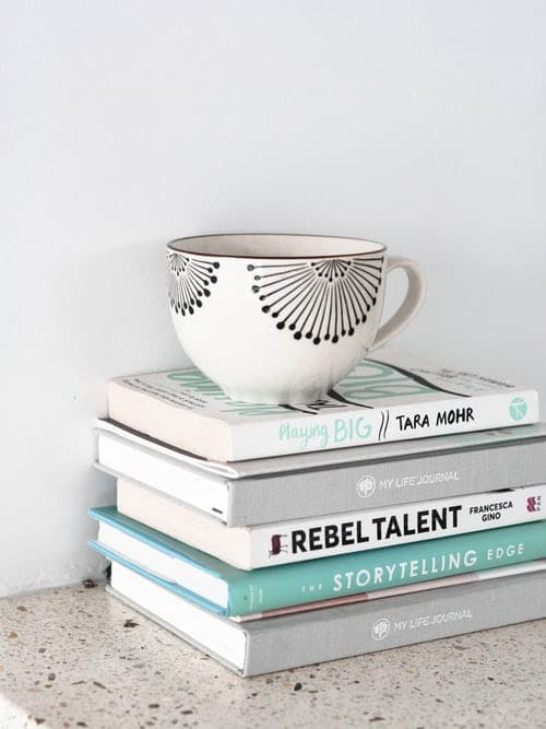 A stack of books with a coffee cup on top.