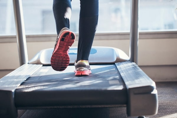 A resident running on a treadmill at Ivy Interbay apartment's gym