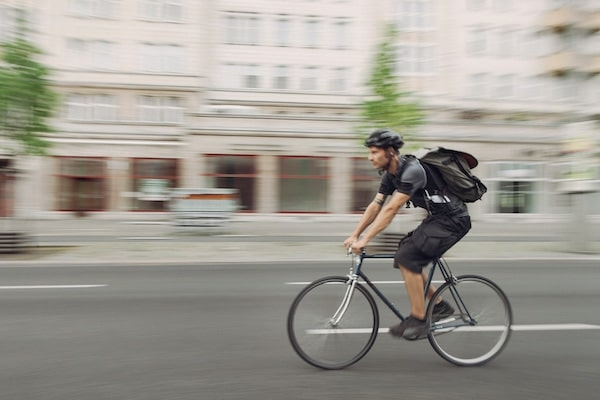 A bicycle messenger riding near Ivy Interbay apartment's bike paths