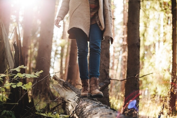 a person wearing boots walking on a tree log with trees in the background.