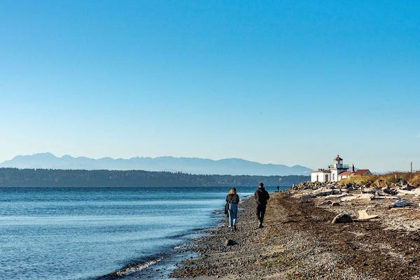 Two people hiking at the beach in Seattle by Interbay with Discover Park in the mid right of the image.